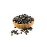 Hölzerne Schüssel trockene schwarze Bohnen lokalisiert auf Weiß Stockfoto