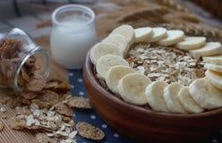 Hölzerne Schüssel von organischen Corn-Flakes und von Hafermehl mit Banane Nahrhaftes Frühstück, rohe Lebensmittelinhaltsstoffe Stockfotos