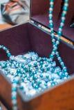 Hölzerne Schatulle mit blauen Perlen und Bonbons stockfotos