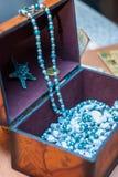 Hölzerne Schatulle mit blauen Perlen und Bonbons stockfotografie