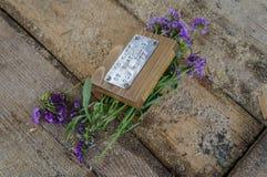 Hölzerne Schatulle mit Blumen auf einem hölzernen Hintergrund mit Sägemehl stockfoto
