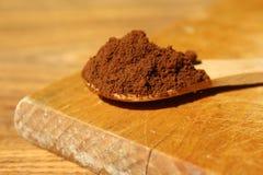 Hölzerne Schaufel mit gemahlenem Kaffee auf einem braunen hölzernen Hintergrund Stockfotografie