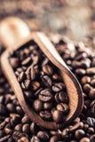 Hölzerne Schaufel voll von Kaffeebohnen auf altem eichenem Tisch Lizenzfreies Stockfoto