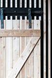 Hölzerne Scheunentür auf Rollen in der Dachbodenart und rustikal Stockfotografie