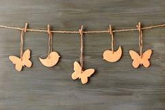 Hölzerne Schmetterlinge und Vögel auf einer Schnur Stockbild