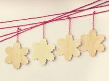 Hölzerne Schneeflocken, die an den roten Schnüren hängen Stockbilder