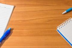 Hölzerne Schreibtischtabelle des Büros mit Notizbuch und Versorgungen Mit Kopien-SP lizenzfreie stockbilder