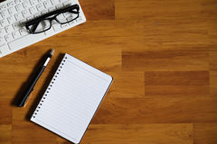Hölzerne Schreibtischtabelle mit Laptop, Notizbuch und Versorgungen Stockfotos
