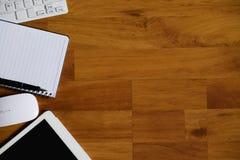 Hölzerne Schreibtischtabelle mit Laptop, Notizbuch und Versorgungen Stockfoto