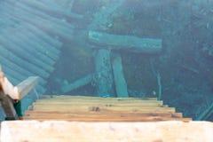Hölzerne Schritte, die in klares blaues Wasser, Trinkwasser, Umwelt, Ökologie, sichtbare Unterseite durch Wasser absteigen stockfotografie