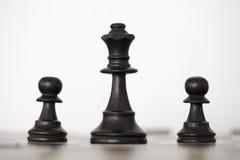 Hölzerne schwarze Königin und zwei Pfandschachfiguren Lizenzfreie Stockbilder