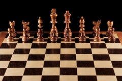 Hölzerne schwarze Schachzahlen auf einem Schachbrett Stockfotos