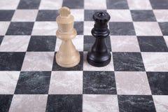 Hölzerne Schwarzweiss-Könige auf Schachbrett Stockfoto