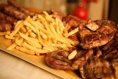 Hölzerne Servierplatte mit Braten und Pommes-Frites Stockfotos