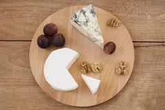 Hölzerne Servierplatte mit Käse Stockfotos