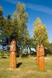 Hölzerne Skulpturen in der Wiese vor Bäumen Stockfoto
