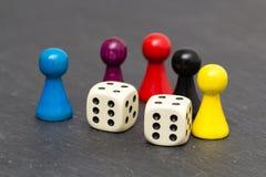 Hölzerne Spielstücke auf dunklem Schiefer Lizenzfreies Stockfoto