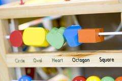 Hölzerne Spielwaren zu lernen und Spiel mit Formen und selektiven f zu färben Lizenzfreies Stockfoto