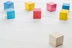 Hölzerne Spielzeugwürfel auf einem weißen hölzernen Hintergrund Lizenzfreies Stockfoto