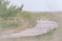 Hölzerne Spur, die führt, um im regnerischen Wetter auf den Strand zu setzen Lizenzfreies Stockbild