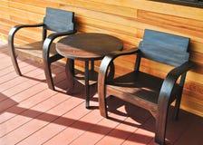 Hölzerne Stühle auf Eingangsterrasse am Beleuchtungsmorgen Stockfoto