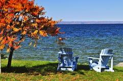 Hölzerne Stühle auf Herbstsee Stockfotografie