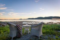 Hölzerne Stühle am Sonnenuntergang auf Strand Stockfoto