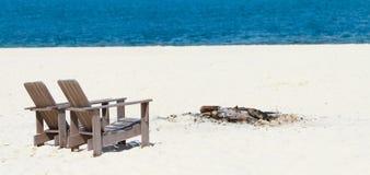 Hölzerne Stühle am tropischen Strandpanorama Lizenzfreie Stockfotos