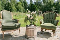 Hölzerne Stühle und Tabelle der Weinlese mit Blumendekoration im Garten outdoor lizenzfreies stockbild