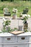 Hölzerne Stühle und Tabelle der Weinlese mit Blumendekoration im Garten outdoor stockbilder