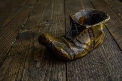 Hölzerne Stiefel in den warmen Farben auf dem hölzernen Hintergrund Stockfoto