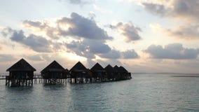 Hölzerne Straße von der Insel zu einer Hütte über Wasser auf einem Sonnenuntergang maldives stock video