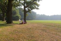 Hölzerne Strandstühle in der ländlichen Landschaft Lizenzfreies Stockfoto