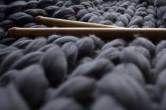 Hölzerne Stricknadeln auf Hintergrund grauen Merinowolle blanke Stockfoto