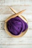 Hölzerne Stricknadeln und purpurroter Merinowolleball in einem Korb Lizenzfreies Stockfoto