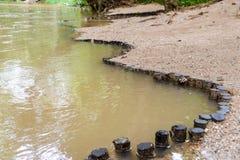 Hölzerne Stummel rudern auf der Flussbank - Dammgrenzfluss lizenzfreie stockfotos