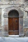 Hölzerne Tür mit Ziegelsteintorbogen. Lizenzfreies Stockbild