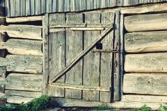 Hölzerne Türen der schönen alten Scheune mit Metallstangen Abbildung der roten Lilie Lizenzfreie Stockbilder
