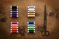 Hölzerne Tabelle der Weinlese mit Spule farbigen Threads und scissor Lizenzfreie Stockfotografie