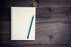 Hölzerne Tabelle des Büros mit leerem Notizblock, Bleistift Lizenzfreie Stockfotos