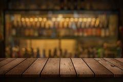 Hölzerne Tabelle mit Blick auf unscharfen Getränkestangenhintergrund Stockfotos