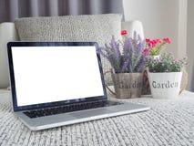Hölzerne Tabelle mit Laptop des leeren Bildschirms und neuer schöner Vielzahl lizenzfreies stockbild