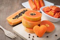 Hölzerne Tabelle mit reifer Papaya der Scheibe und orange Herz formen Zeichen an Stockfotos