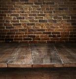 Hölzerne Tabelle mit Ziegelsteinhintergrund Stockfoto