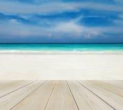Hölzerne Terrasse auf dem Strand mit klarem Himmel, blauem Meer und Copyspace auf weißem Sand für Spott bis zum Anzeigen-Produkt  Lizenzfreies Stockfoto