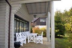 Hölzerne Terrasse des alten Landhauses mit weißem Holzmöbel lizenzfreie stockfotografie