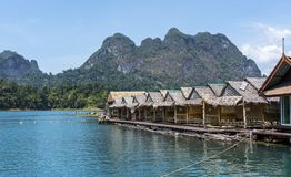 Hölzerne thailändische traditionelle sich hin- und herbewegende Häuser auf einem See mit Bergen und Regenwald im Hintergrund währ Lizenzfreie Stockfotos