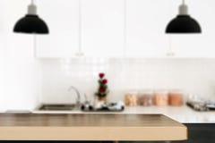 Hölzerne Tischplatte als Kücheninsel auf Unschärfeküchenhintergrund - lizenzfreies stockbild