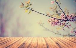 Hölzerne Tischplatte auf Blumenhintergrund Lizenzfreies Stockfoto