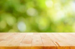 Hölzerne Tischplatte auf bokeh Zusammenfassungs-Grünhintergrund Lizenzfreie Stockbilder